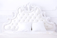 white headboard of a bed in classical style in a light bedroom