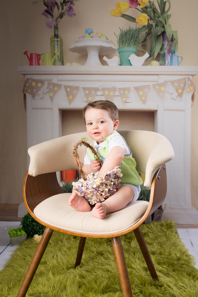 hand in the flower basket looking for Easter eggs with a home like Easter backdrop with a green fluffy rug