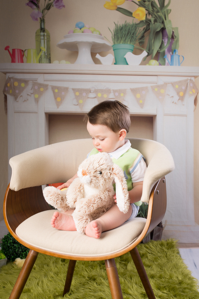 Easter bunny stuffed animal on his lap. He is looking down something unknown with a backdrop Easter like eggs in the background
