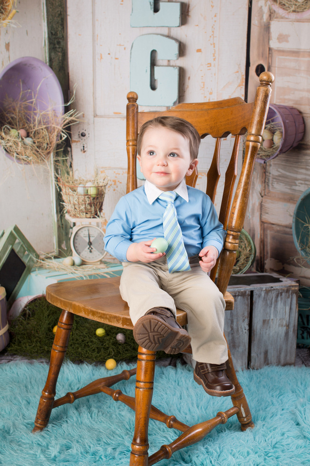 in his Easter outfit while holding a green Easter egg