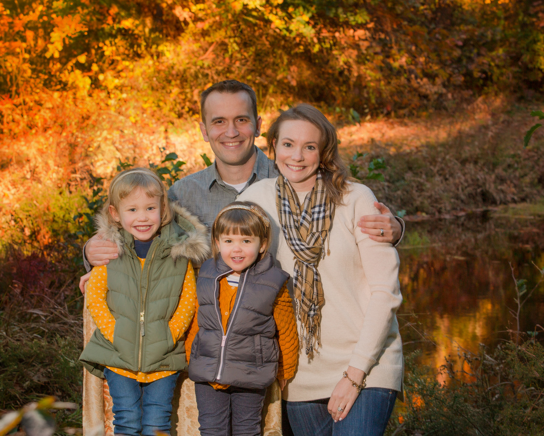 Family photo with a orange and green background. family looking happy in their fall colors with a lake behind them