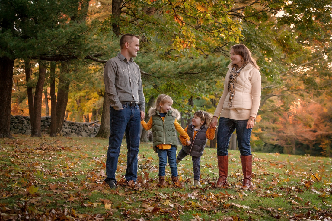 Family all looking at each other smiling with lots of trees behind them also a small stone wall