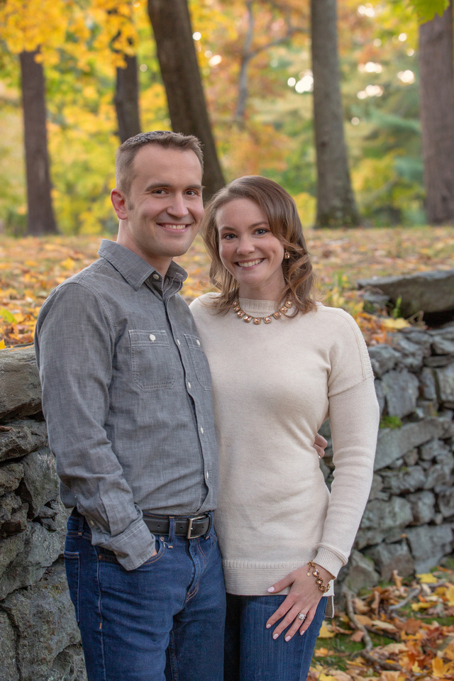 Happy couple in front of a stone wall with the yellow leaves, green leaves. and brown trees in the background