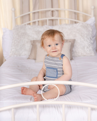baby on cream rug white back drop