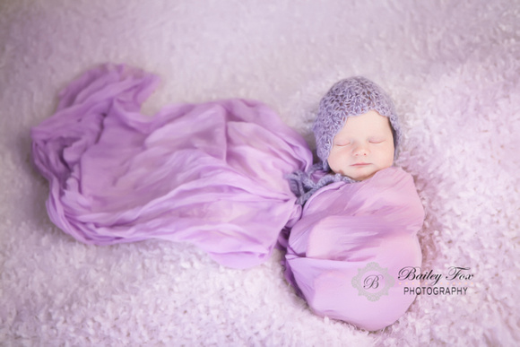 Rhode island newborn photography by bailey fox baby wrapped in purple with a purple bonnet