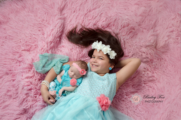 image taken from above of 11 year old sister with her newborn baby girl sister