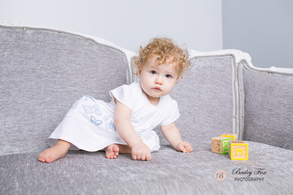 beautiful baby near her first birthday chilling on a gray vintage sofa playing with blocks